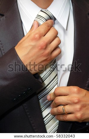man hands remedying a tie