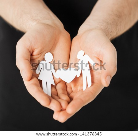 man hands showing two paper men with heart shape - stock photo