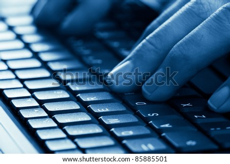 man hands typing on laptop keyboard blue toned with shallow depth of field - stock photo