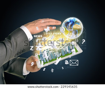 Man hands using tablet pc. Business city on touch screen. Earth with flying letters near computer. Elements of tgis image furnished by NASA