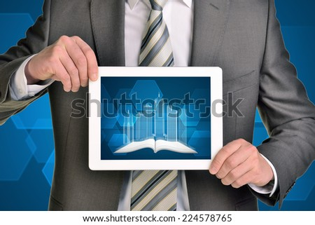Man hands using tablet pc. Image of wire-frame buildings and open book on tablet screen