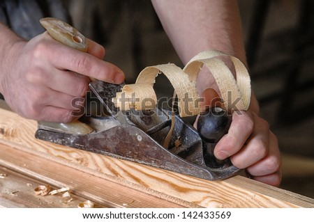 Man hands with carpenters plane on wooden background