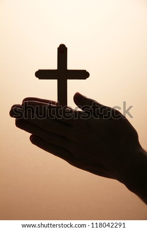 man hands with crucifix, on brown background