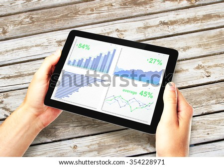 Man hands with digital tablet with business chart on a screen on wooden table