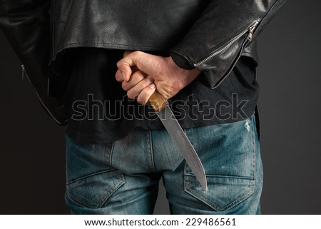 man hands with knife on gray background - stock photo