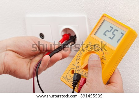 Man hands with multimeter checking voltage in a wall fixture - stock photo