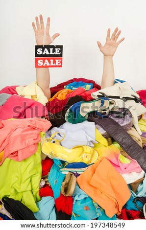 Man hands with the sale sign reaching out from a big pile of clothes and accessories.Man buried under an untidy cluttered woman wardrobe.Man reaching for help from to much woman shopping on clearance. - stock photo