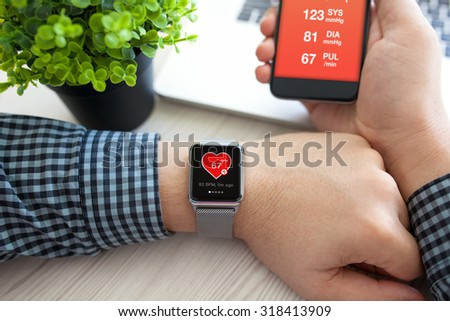 Man hands with watch and phone with app health on the screen - stock photo