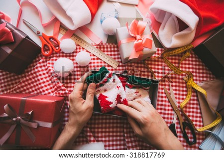 Man hands wrapping modern Christmas gifts presents at home. - stock photo