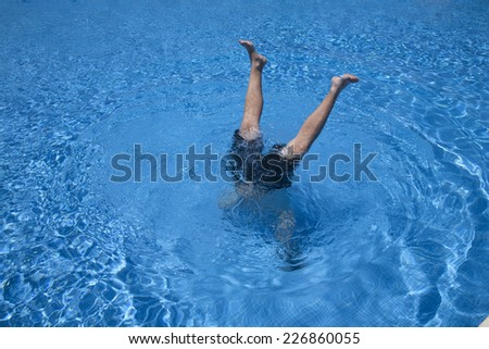 man handstands underwater with two legs peering in a blue pool - stock photo