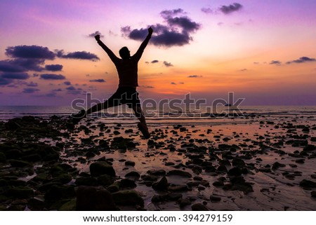 man Happy jump with his hands up during sunset at the beach. - stock photo