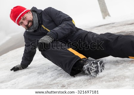 Man has an accident on a icy Street - stock photo