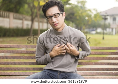 Man has chest pain at park - stock photo
