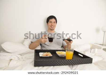 Man having a breakfast and watching tv