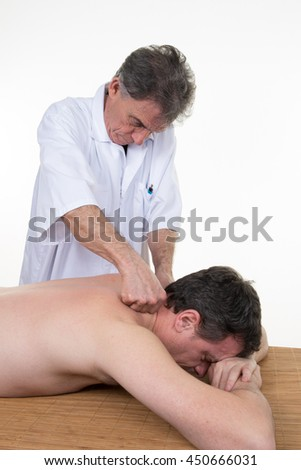 Man having a massage in a wellness center by therapist - stock photo