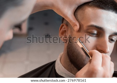 Man having a shave at the barber shop. - stock photo