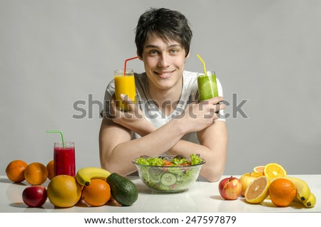 Man having a table full of organic food,juices and smoothie. Cheerful young man eating healthy salad and fruits. Isolated on white - stock photo