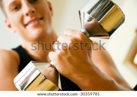 Man having a workout with dumbbell in the gym (Focus on dumbbell!) - stock photo