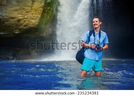 man having an adventurous tracking with camera near the waterfall in bali - stock photo
