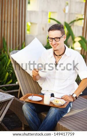 man having breakfast in garden in summer - stock photo