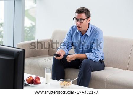 Man having breakfast while watching something shocking on tv - stock photo