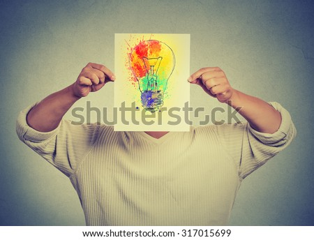 Man having brilliant idea colorful lightbulb covering face isolated grey wall background. Free thinking, new approach, alternative technology. Creativity, imagination, dynamism, intelligence concept - stock photo