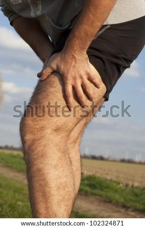Man having cramp while running - stock photo