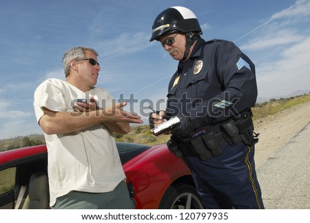 Man having discussion with police officer by car - stock photo