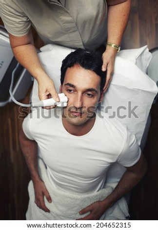 Man having facial laser rejuvenation procedure in aesthetic clinic, handsome man sitting in the medical chair in cabinet of beauty salon  - stock photo