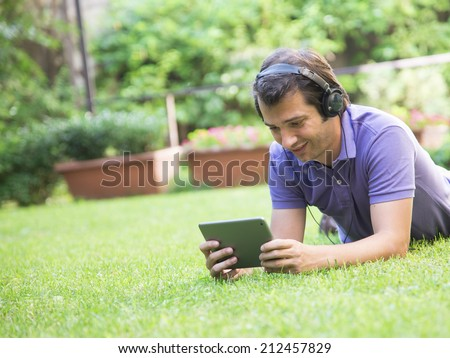 man having fun and relax with music and tablet internet - stock photo