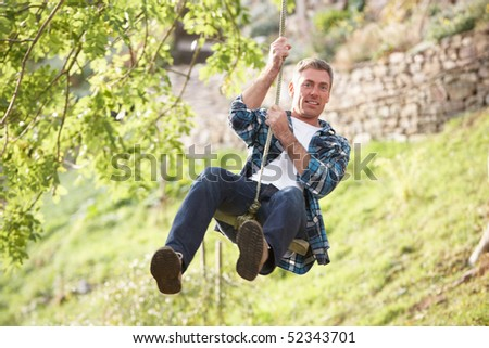 Man Having Fun On Woodland Swing In Autumn - stock photo