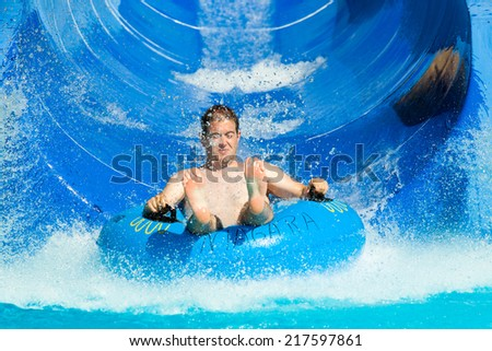 Man having fun, sliding at water park.
