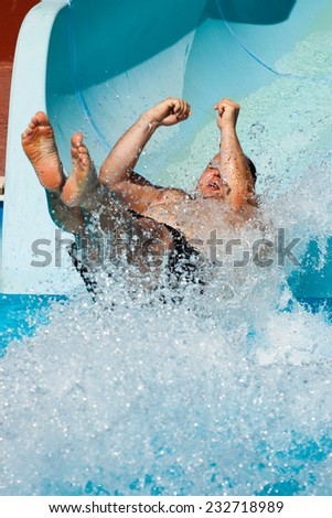 Man having fun, sliding at water park. - stock photo