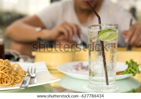 Man having glass of fresh sparkling mineral water with his dinner
