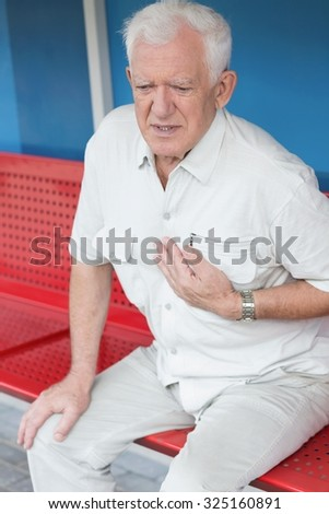 Man having heart attack on the bus stop - stock photo