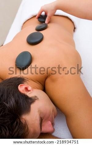 Man having hot stone massage - stock photo
