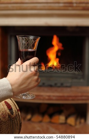 Man having red wine by the fireplace - stock photo