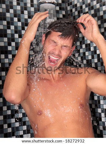 Man having shower in bathroom with soap and shampoo - stock photo