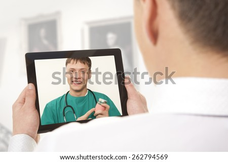 Man having video chat with doctor on laptop at home - stock photo