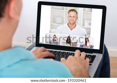 Man having video conference with friends on laptop at home - stock photo