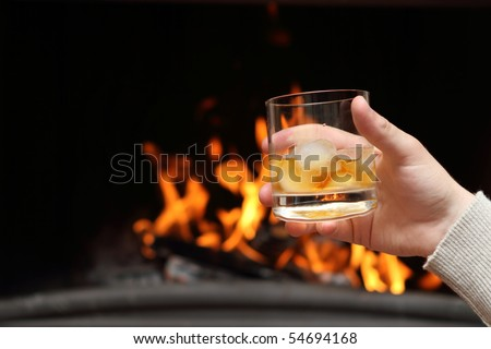 Man having whiskey by the fireplace - stock photo