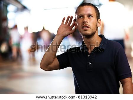 man hearing sounds at shopping center - stock photo