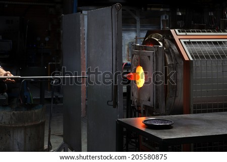 man heating glass in furnace in studio - stock photo