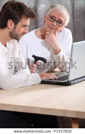 Man helping an elderly lady with her laptop - stock photo