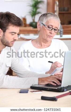 Man helping elderly lady - stock photo