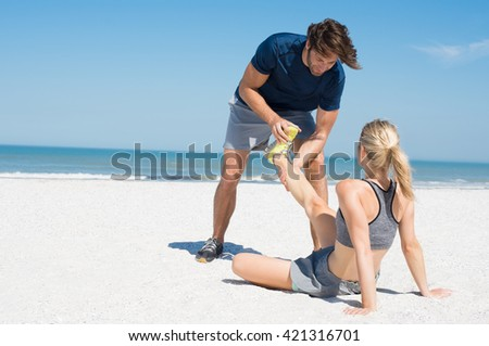 Man helping female runner in pain. Woman athlete having cramp during run. Sports woman with twisted sprained ankle, copys space.  - stock photo