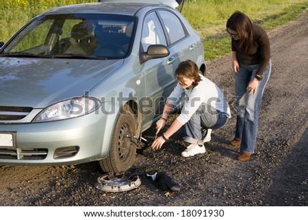 man helping for woman to change broken wheel - stock photo