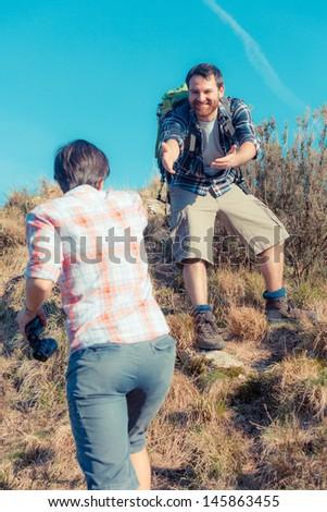 Man Helping His Girlfriend Hiking - stock photo