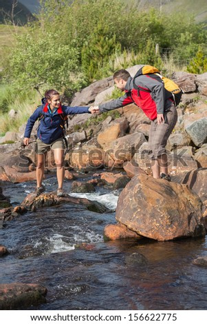 Man helping his girlfriend to cross a river carrying backpacks on a hike - stock photo