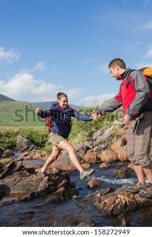 Man helping his girlfriend to cross a stream on a hike in the countryside - stock photo